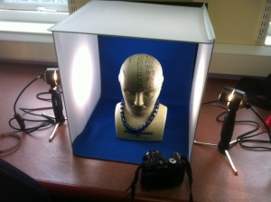 Photo studio booth with lights and a Phrenology head and an SLR camera